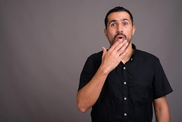 Bel uomo barbuto contro il muro grigio