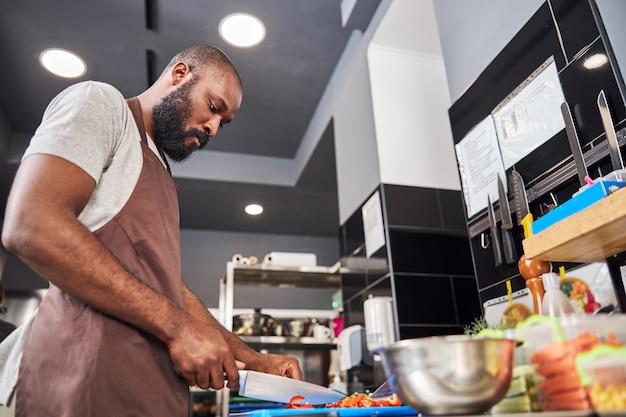 Bell'uomo barbuto in grembiule che taglia le verdure con il coltello per preparare il ripieno