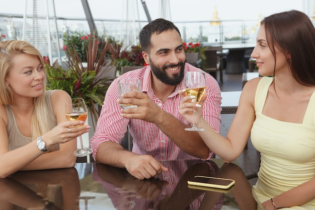 Bell'uomo barbuto in chat con le sue amiche, bevendo al bar con terrazza