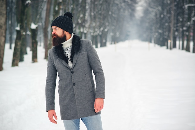 Uomo barbuto bello in cappotto e cappello in inverno