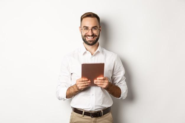 Bel uomo barbuto in bicchieri utilizzando tavoletta digitale, sorridendo soddisfatto, in piedi su sfondo bianco.