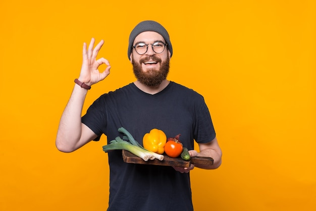 L'uomo barbuto bello che tiene un tagliere con alcune verdure sta mostrando il gesto giusto.