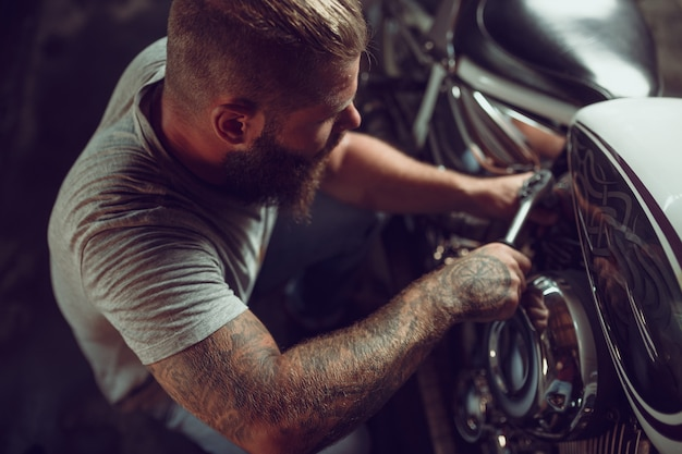 L'uomo barbuto bello in bomber e occhiali da sole sta sedendosi sulla motocicletta nell'officina riparazioni