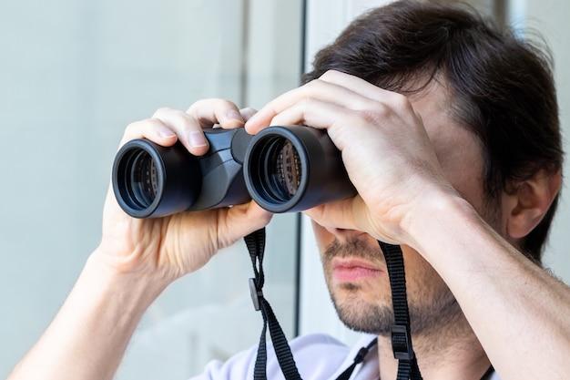 Bel uomo barbuto guardando attraverso il binocolo