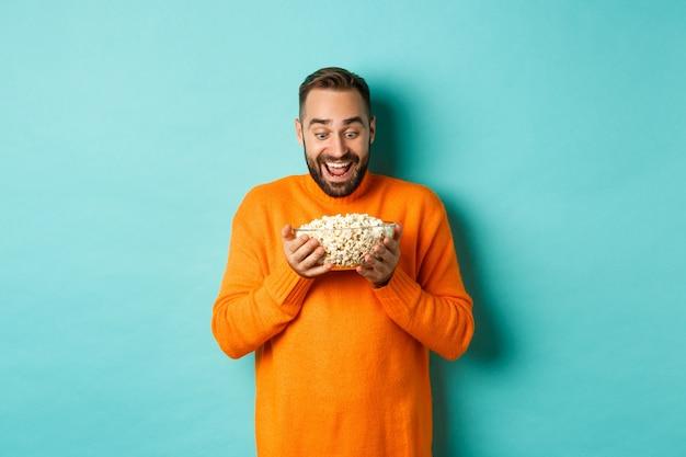 Bel uomo barbuto guardando con exctied e felice alla ciotola di popcorn, pronto per guardare film, in piedi su sfondo bianco.