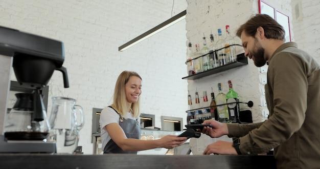 Bell'uomo barbuto che paga il caffè da asporto con il cellulare al bar. operaio al servizio di un cliente che utilizza lo smartphone per pagare in una caffetteria.