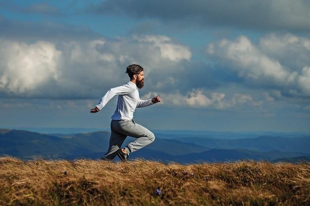 Uomo barbuto bello che corre sulla montagna