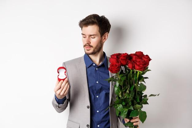 Bel uomo barbuto in tuta guardando l'anello di fidanzamento, rendendo la sorpresa il giorno degli innamorati, in piedi con rose rosse su sfondo bianco.