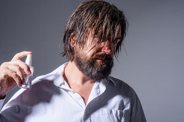 Bell'uomo barbuto con una bottiglia di cosmetici per profumi che pubblicizzano cosmetici per fragranze di profumi maschili