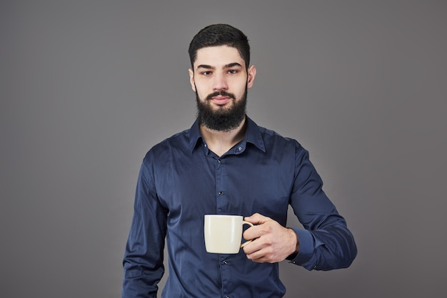 Uomo barbuto bello con barba e baffi capelli alla moda sul viso serio in camicia che tiene tazza o tazza bianca bere tè o caffè in studio su sfondo grigio.