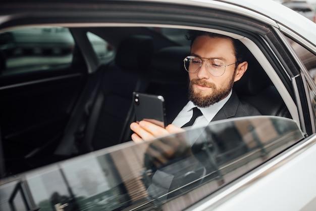 Uomo d'affari bello, barbuto e sorridente che chiama al telefono sul sedile posteriore dell'auto
