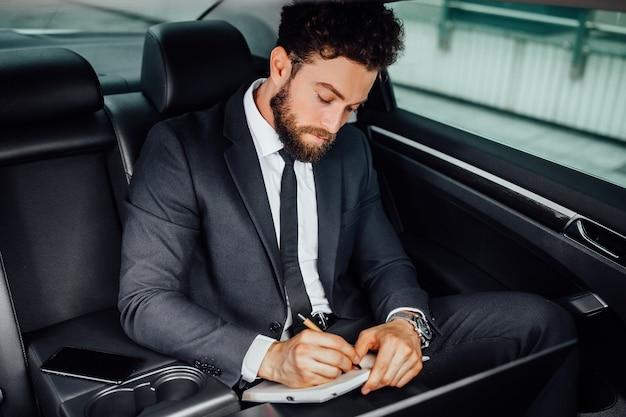 Uomo d'affari bello, barbuto e sorridente che lavora sul sedile posteriore dell'auto e prende appunti sul taccuino