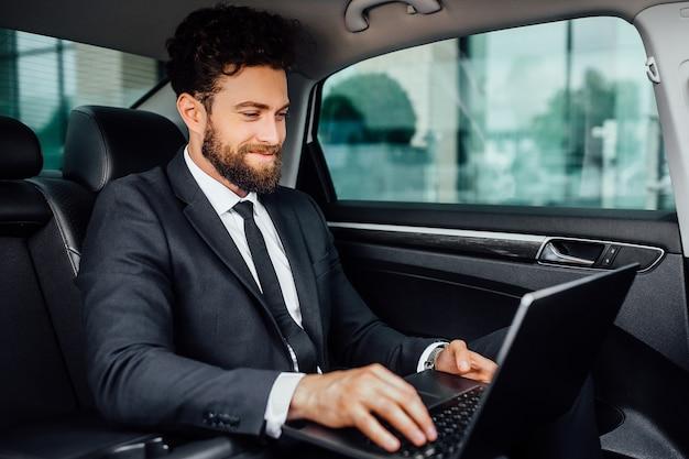 Un manager bello, barbuto e sorridente che lavora al suo laptop sul sedile posteriore dell'auto