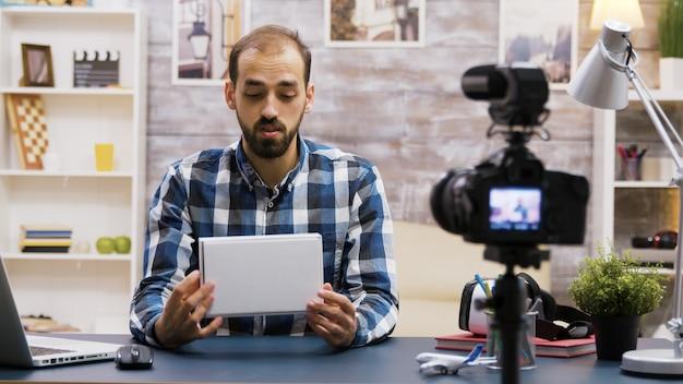 Bello vlogger barbuto che registra una recensione mentre tiene in mano una scatola. creatore di contenuti online.