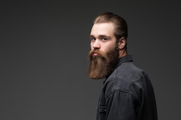 Giovane uomo barbuto bello dei pantaloni a vita bassa isolato su fondo grigio