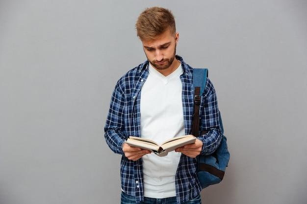 Bel giovane barbuto in camicia a scacchi con libro di lettura zaino isolato su un muro grigio