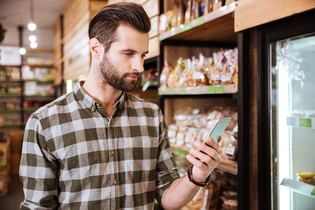 Bel giovane barbuto in camicia a quadri usando il cellulare nel negozio di alimentari