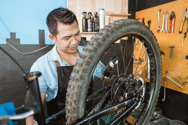 Il bel meccanico della bicicletta in grembiule indossa i guanti mentre tiene la bottiglia mentre usa lo spray lubrificante