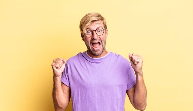 Bell'uomo adulto biondo sentirsi scioccato, eccitato e felice, ridendo e celebrando il successo, dicendo wow!