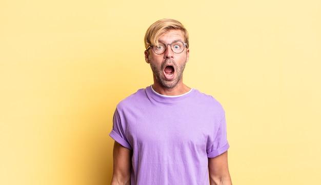 Bell'uomo adulto biondo che sembra molto scioccato o sorpreso, fissando con la bocca aperta dicendo wow
