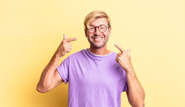 Uomo adulto biondo bello che sorride con sicurezza indicando il proprio ampio sorriso, atteggiamento positivo, rilassato e soddisfatto