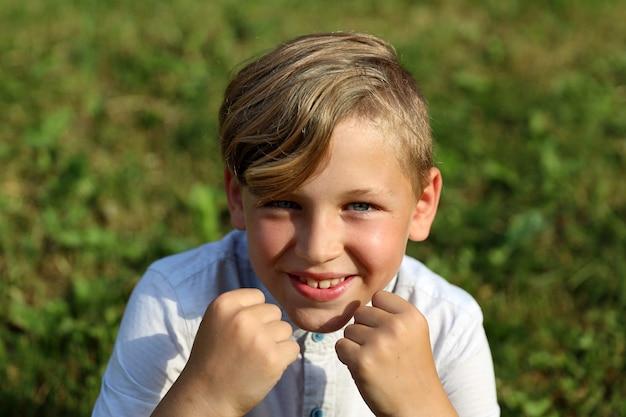 Bel ragazzo biondo seduto sull'erba in estate nel parco. foto di alta qualità