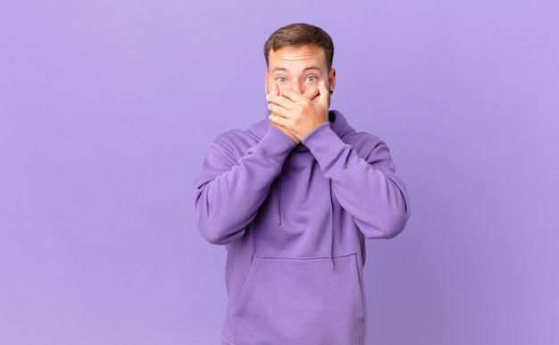Bell'uomo biondo che copre la bocca con le mani con uno shock