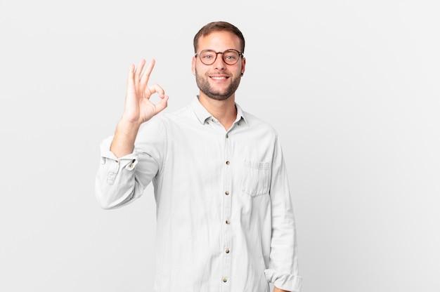 Un bell'uomo biondo che si sente felice, mostra approvazione con un gesto ok