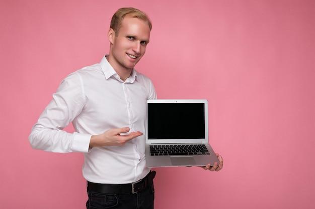 Bell'uomo biondo che tiene il computer portatile del computer con lo schermo del monitor vuoto con mock up e