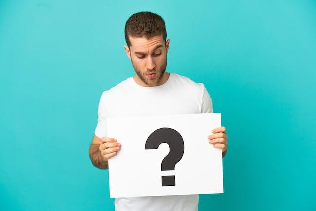 Uomo biondo bello sopra fondo blu isolato che tiene un cartello con il simbolo del punto interrogativo