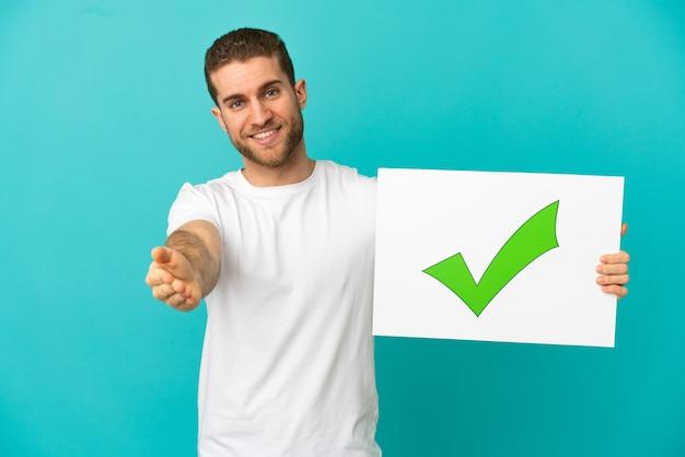 Bel uomo biondo su sfondo blu isolato che tiene un cartello con testo icona segno di spunta verde che fa un affare
