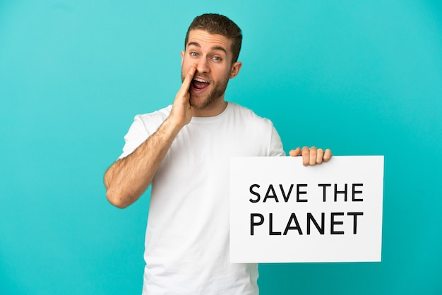 Uomo biondo bello sopra fondo blu isolato che tiene un cartello con testo salva il pianeta e grida