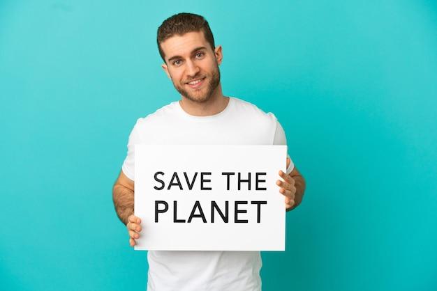 Uomo biondo bello sopra fondo blu isolato che tiene un cartello con testo salva il pianeta con espressione felice