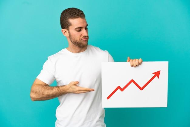 Bel uomo biondo su sfondo blu isolato con in mano un cartello con un simbolo di freccia in crescita statistica e puntandolo