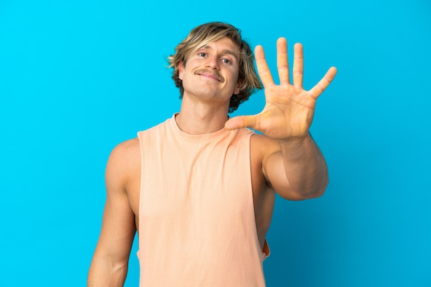 Uomo biondo bello isolato contando cinque con le dita