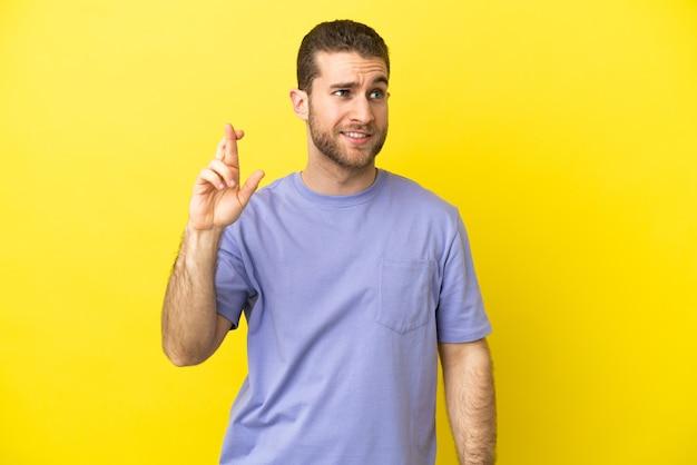 Bell'uomo biondo su sfondo giallo isolato con le dita incrociate e augurando il meglio