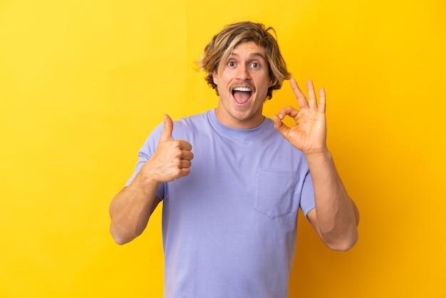 Uomo biondo bello isolato su giallo che mostra segno giusto e pollice sul gesto