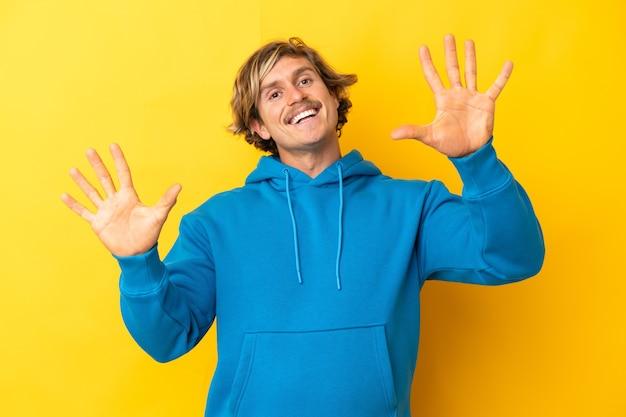 Uomo biondo bello isolato sulla parete gialla che conta dieci con le dita