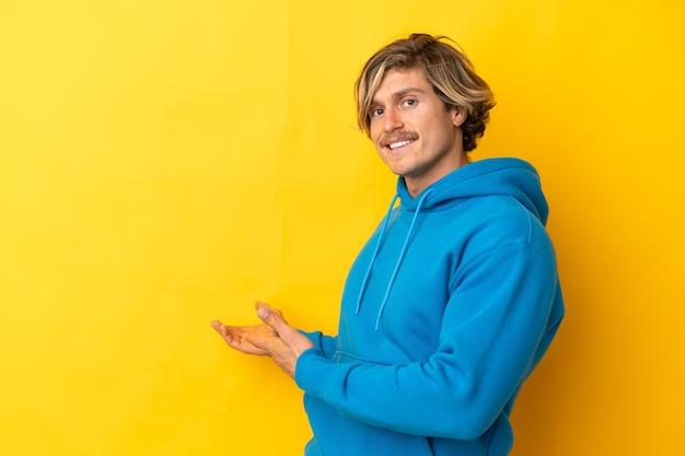 Uomo biondo bello isolato sulla parete gialla che estende le mani a lato per invitare a venire
