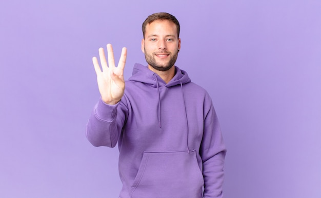 Bell'uomo biondo che sorride e sembra amichevole, mostrando il numero quattro