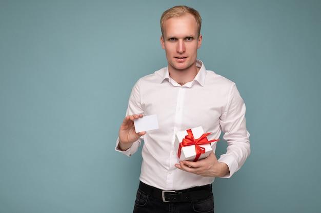 Un bell'uomo biondo che indossa una camicia bianca isolata su una parete di fondo blu che tiene in mano una carta di credito e una confezione regalo guardando la fotocamera
