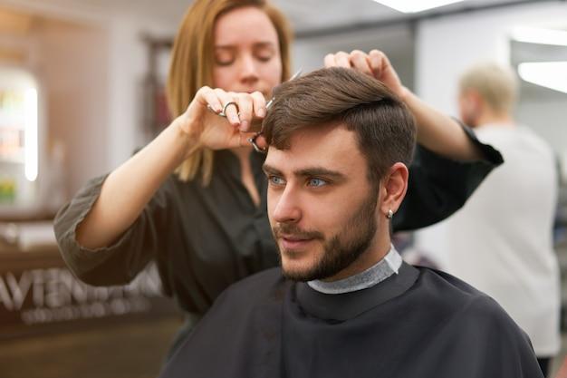 Bel uomo dagli occhi blu seduto nel negozio di barbiere. parrucchiere parrucchiere donna che taglia i capelli. barbiere femminile.