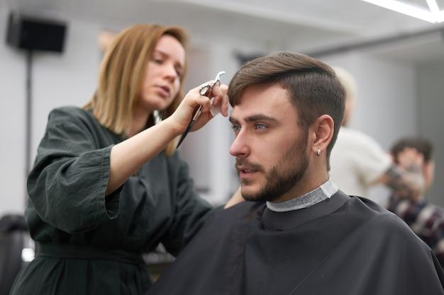 Bel uomo dagli occhi blu seduto nel negozio di barbiere. parrucchiere parrucchiere donna che taglia i suoi capelli. barbiere femminile.