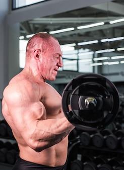 Uomo bello bodybuilder con grandi muscoli in palestra