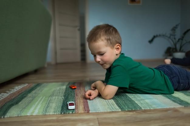 Bel ragazzo sdraiato sul pavimento sul tappeto gioca con le macchinine.