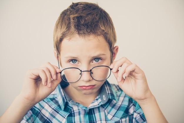 Bel ragazzo che prova su grandi occhiali