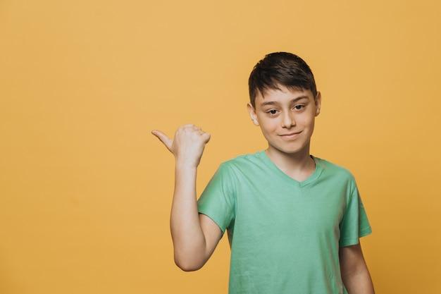 Bel ragazzo con gli occhi marroni vestito con una maglietta verde, indica lo spazio della copia con il dito pollice, sorridente carino, soddisfatto, approvando la scelta. concetto di vendita