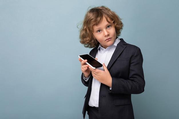 Bel ragazzo con i capelli ricci che indossa tuta tenendo il telefono