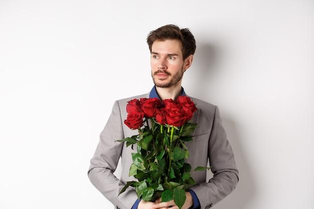 Bel ragazzo in tuta andando ad un appuntamento romantico, tenendo in mano il mazzo di rose rosse e guardando a sinistra pensieroso, in piedi su sfondo bianco.
