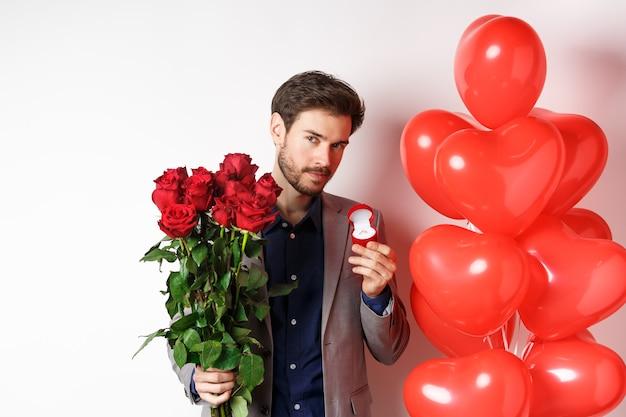 Bel ragazzo in abito che fa proposta il giorno degli innamorati, che tiene l'anello di fidanzamento e rose rosse, prepara fiori a sorpresa e palloncini a cuore per la fidanzata su san valentino, sfondo bianco.